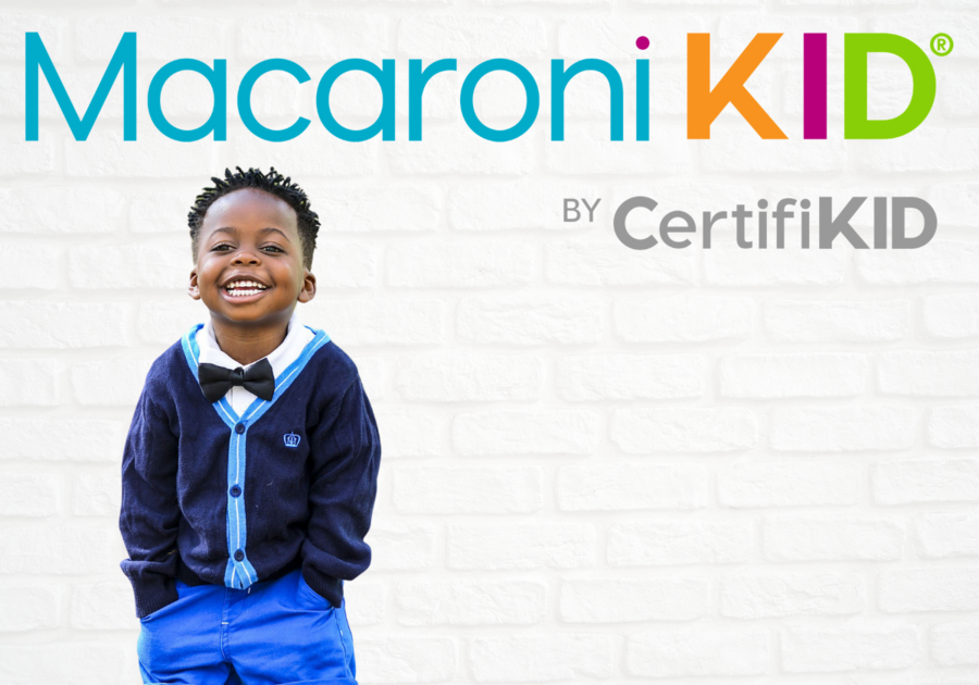 new Macaroni Kid logo with litlle boy smiling against wall