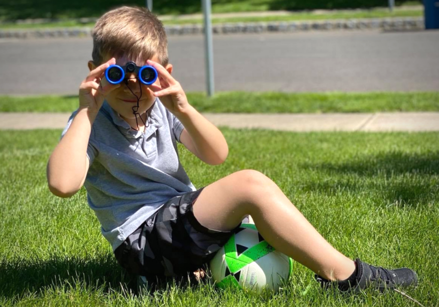 little boy on lawn looking through binoclulars
