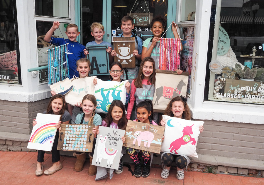 Group of children standing outside of AR Workshop building holding canvas and macrame crafts
