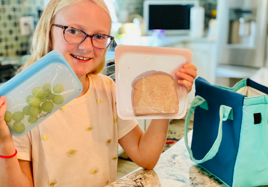 Little girl showing her lunch packed in reusable Stasher bags