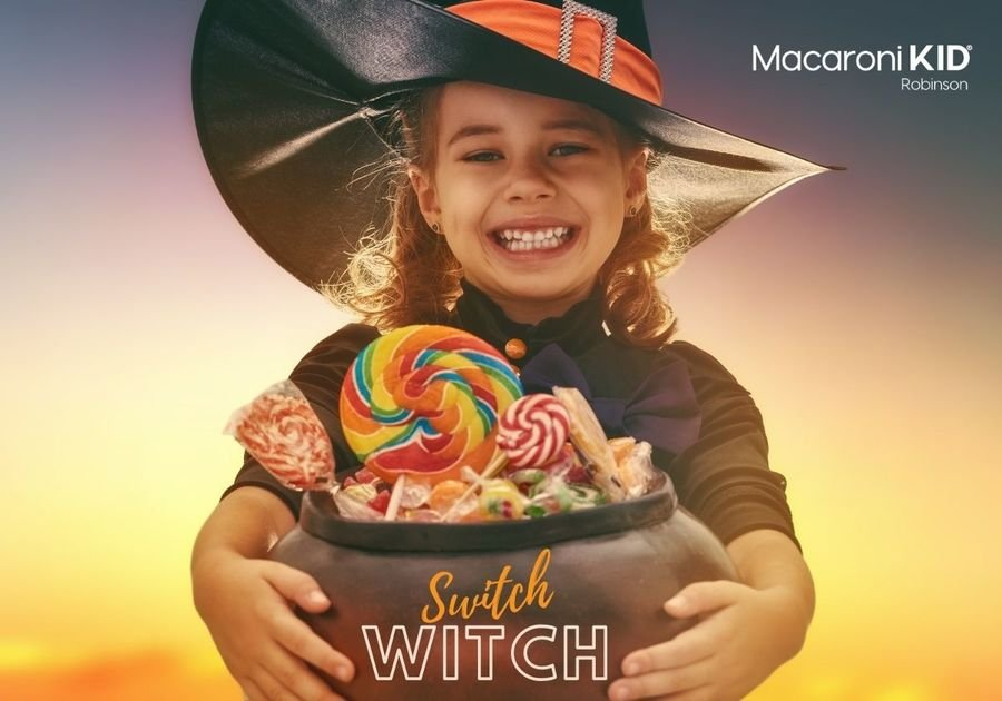 Little girl dressed in a witch costume holding a cauldron of candy