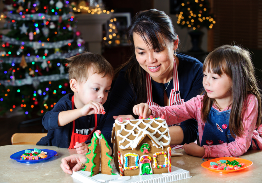 Mom and kids decorating gingerbreadhouse