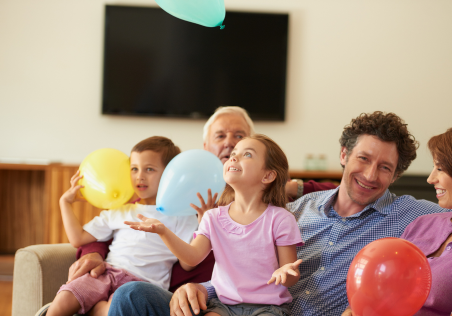 Family smiling on couch holding balloons